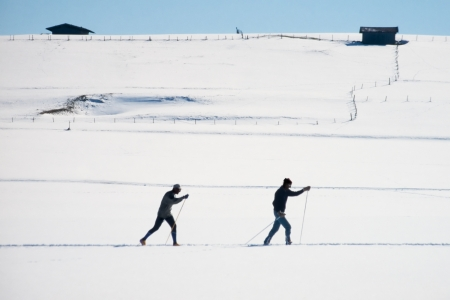expanse: Two active cross country skiers following an x-country ski track across a flat expanse of winter snow exercising winter sports Stock Photo