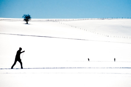 Active cross country skier following an x-country ski track across a flat expanse of winter snow exercising winter sports photo