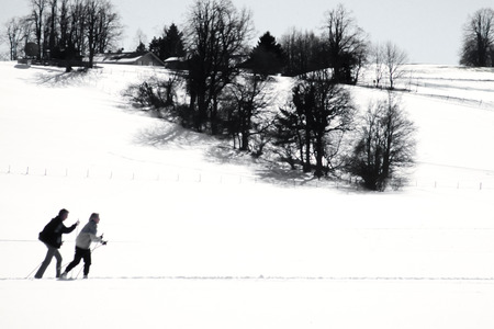 Two active cross country skiers following an x-country ski track across snowy winter landscape exercising winter sports