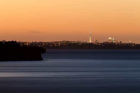 highriser: Distant skyline of Auckland City, New Zealand, with Sky Tower illuminated in twilight dusk after sunset