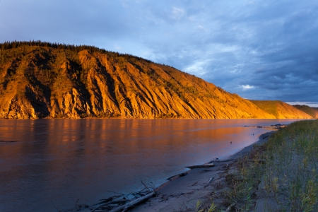 yukon: Eroded clay cliff river bank at Yukon River, Yukon Territory, Canada, near Dawson City glowing in orange light of summer sunset sun Stock Photo