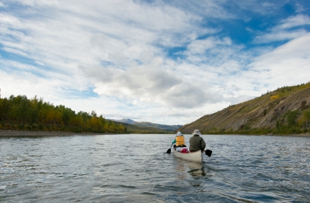 A couple of canoeists on wilderness adventure trip paddling wide Pelly River, central Yukon Territory, Canada