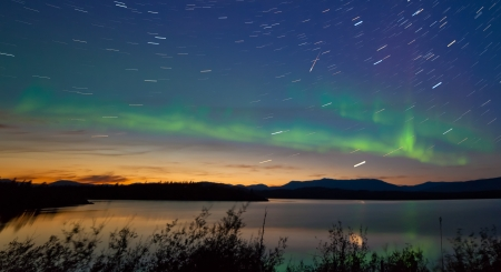 Northern lights  Aurora borealis and shooting star meteor at midnight in summer over northern horizon of Lake Laberge  Yukon Territory  Canada  at early dawn Фото со стока