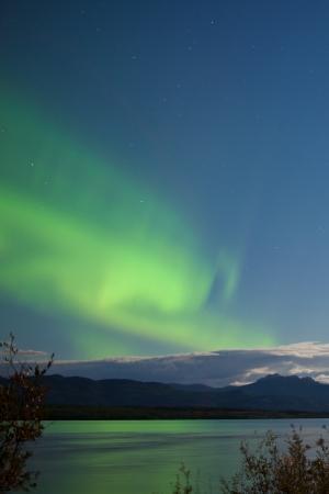 magnetosphere: Aurora boreale verdi, Aurora boreale, il cielo notturno con nuvole al chiaro di luna e le stelle sopra boreale foresta taiga del lago Laberge, Yukon Territory, Canada