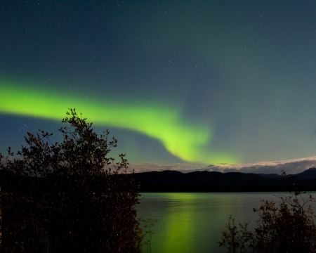 aurora borealis: Band of green northern lights, Aurora borealis, on night sky mirrored on Lake Laberge, Yukon Territory, Canada Stock Photo