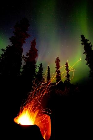 trails of lights: Aperto fal� che brucia caldo in ghisa pozzo del fuoco con percorsi scintilla volare in boreale foresta taiga sotto le luci del nord, Aurora borealis