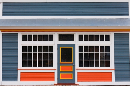Symmetrical view of the front door and entrance to a quaint colorful wooden house with large cottage pane windows on either side