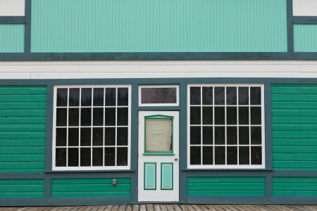 Symmetrical view of the front door and entrance to a quaint green wooden house with large cottage pane windows on either side