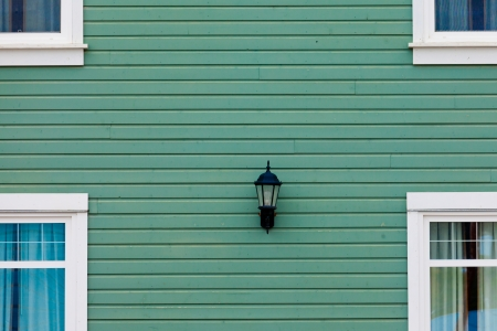 centered: Green building facade with windows around centered exterior lamp as architecture background pattern abstract