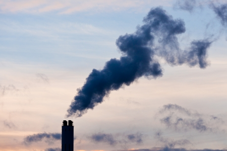 Smokestack chimney belching black smoke and pollutants in blue evening sky contributing to global warming and climate change Stock Photo