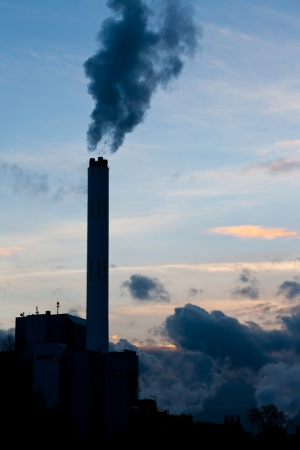 emissions: Smokestack chimneys belching black smoke pollutants and carbon dioxide greenhouse gas into the atmosphere polluting and contributing to global warming