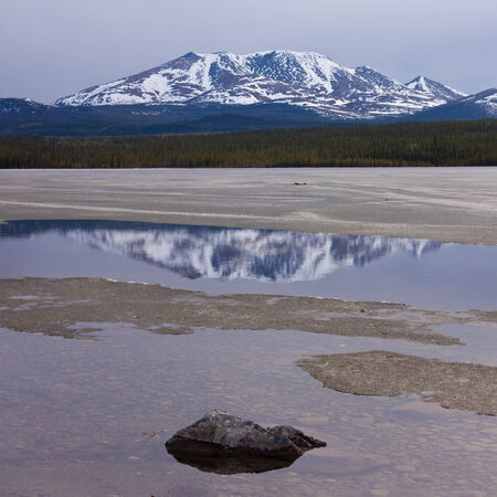 snowcapped: Spring break-up at Fox Lake, Yukon Territory, Canada, still snowy Little Peak reflection on open shore water and rock mimicking a small mountain