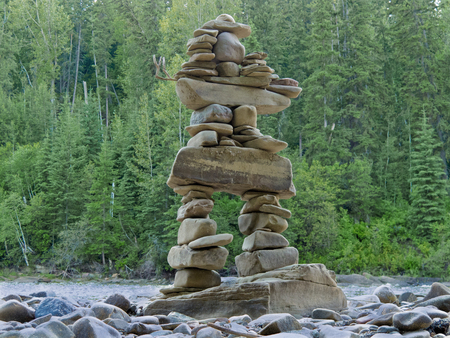 inukshuk: Large rocks stacked and balanced to form an Inuksuk stone landmark or cairn as a marker or monument in front of boreal forest taiga wilderness terrain