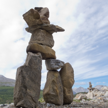 Large rocks stacked and balanced to form an Inuksuk stone landmark or cairn as a marker or monument in mountainous wilderness terrain