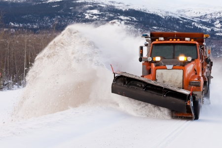 Snow plough truck clearing road after whiteout winter snowstorm blizzard for vehicle access Stock Photo - 24443325