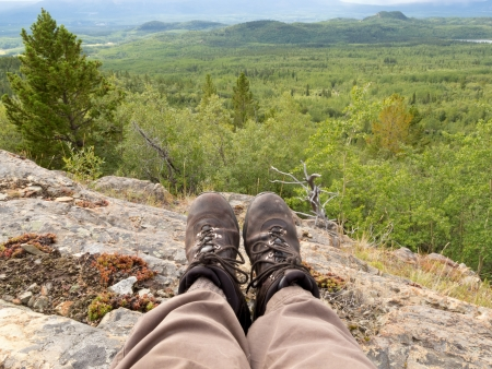 whitehorse: Tired hiker taking a rest from hiking overlooking rocky terrain and beautiful scenery in boreal forest taiga just north outside Whitehorse, Yukon Territory, Canada Stock Photo