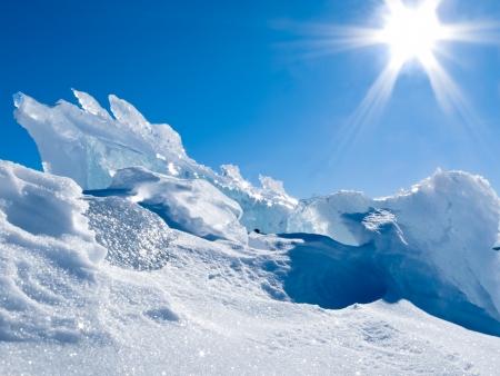 Ijzige hoop ijs brokken gletsjer met wat verse sneeuw en een blauwe zonnige hemel smelten weg