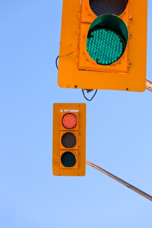 to contradict: Two traffic lights, green and red, confusing and contradicting against blue sky with copyspace