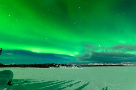 magnetic field: Northern Lights or Aurora borealis or polar lights forming green swirls over frozen Lake Laberge Stock Photo