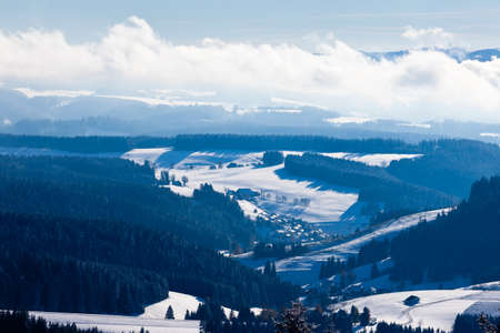 Horizon of foggy mist clouds in snowy winter Black Forest village valley landscape, rural Germany, Europe photo