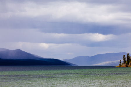 yukon: Dark rain clouds over Fox Lake, Yukon Territory, Canada and distant mountain range Stock Photo