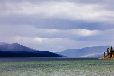 squall: Dark rain clouds over Fox Lake, Yukon Territory, Canada and distant mountain range Stock Photo