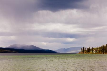 squall: Rain showers over Fox Lake, Yukon Territory, Canada and distant mountain range Stock Photo