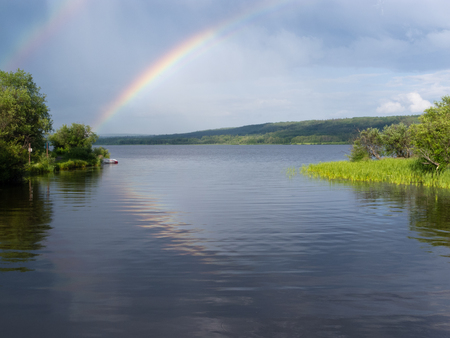 reflected: Rainbow over calm water of northern boreal forest taiga lake, northern British Columbia, Canada Stock Photo