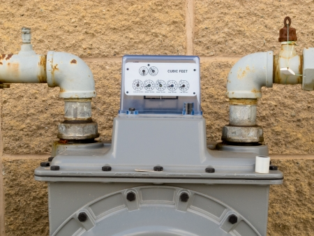 Residential natural gas meter on exterior wall to measure household energy consumption shows reading on dial display 免版税图像