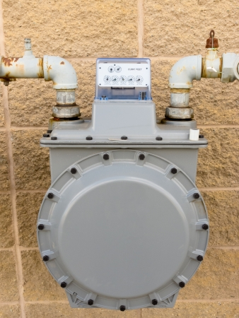 Residential natural gas meter on exterior wall to measure household energy consumption