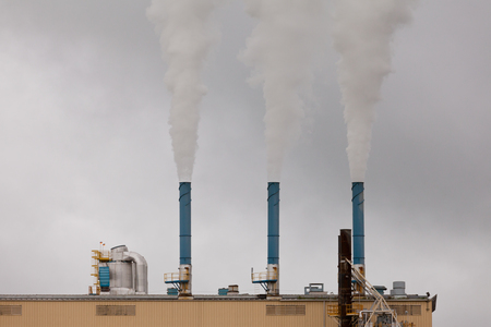 greenhouse gas: Row of three smokestacks on industrial factory plant roof adding grey smoke to grey sky