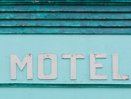 Detail of painted blue-green historic motel wooden grungy facade siding