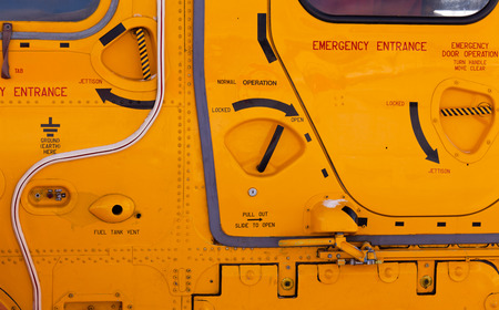 exits: Background detail abstract of emergency handles, entrance hatches and exits on a yellow helicopter exterior Stock Photo