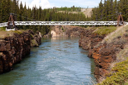 whitehorse: Miles Canyon Yukon River rock cliffs with suspension swing bridge just south of the city of Whitehorse  Yukon Territory  Canada