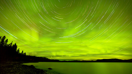 Astrophotography star trails with green glowing display of Aurora borealis or Northern Lights over boreal forest taiga at Lake Laberge, Yukon Territory, Canada photo