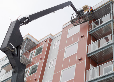 Workmen working on outside of multistorey apartment block using mechanical crane machine with basket on hydraulic extension boom, also called industrial cherry picker Stock Photo