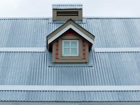 Architectonische details van de kleine dakkapel in metaalplaat dak van woonhuis