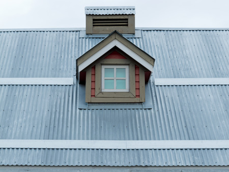 Architectural detail of small dormer window in metal sheet roof of residential house