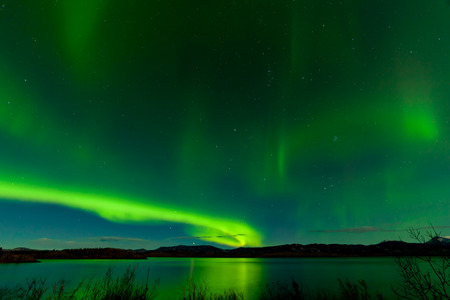 phenomenon: Sparkling green starry night sky show of Aurora borealis or Northern Lights reflections on calm surface of Lake Laberge, Yukon Territory, Canada Stock Photo