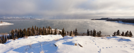 Steaming Lake Laberge, Yukon Territory, Canada, on cold winter day before freeze-up with fox tracks on snowy lake shore