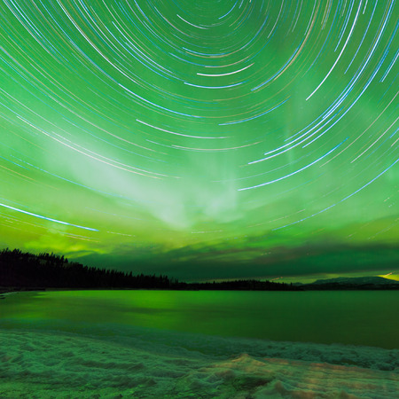 astrophotography: Astrophotography star trails with green sparkling show of Aurora borealis or Northern Lights over boreal forest taiga winter scene of Lake Laberge, Yukon Territory, Canada