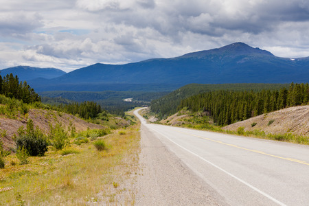 Endless empty road of Alaska Highway, Alcan, crossing wide open expanse boreal forest taiga landscape west of Watson Lake, Yukon Territory, Canada photo