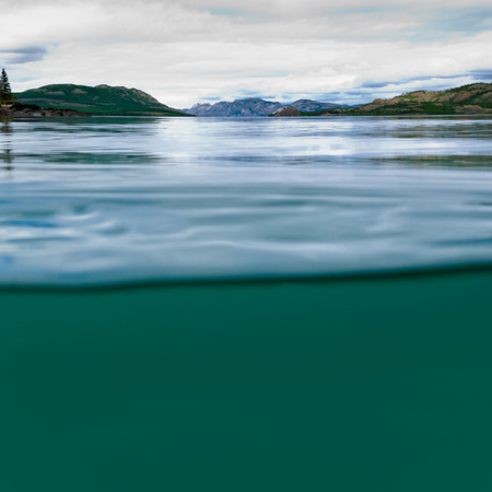 Half underwater half over, over-under split shot of huge Lake Laberge, Yukon Territory, Canada, clear blue freshwater and distant shore boreal forest taiga landscape