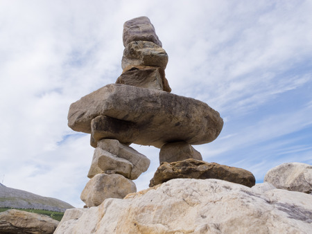 mountainous: Large rocks stacked and balanced to form an Inuksuk stone landmark or cairn as a marker or monument in mountainous wilderness terrain