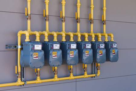 Row of residential natural gas meters and yellow pipe plumbing on exterior wall to measure household energy consumption Standard-Bild