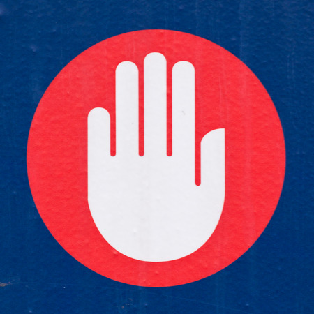Halt or Stop sign showing the palm of a hand calling a halt, bringing an end to something or forbidding entry