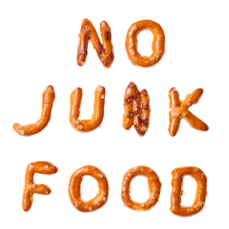 solid food: Words NO JUNK FOOD written, laid-out, with crispy alphabet pretzels isolated on white background