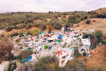 dumped: Pile of rubbish illegally dumped in natural landscape polluting nature environment