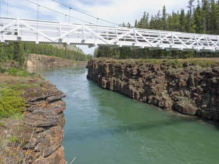 whitehorse: Miles Canyon Yukon River rock cliffs with white painted suspension swing bridge just south of the city of Whitehorse, Yukon Territory, Canada