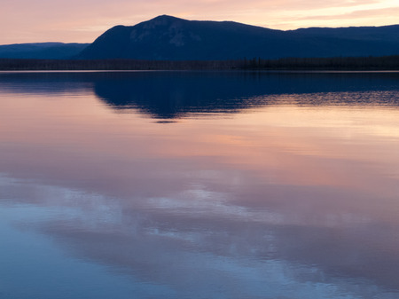 reflected: Reflection of distant sunset boreal forest taiga mountain mirrored on calm water surface of Little Salmon Lake, Yukon Territory, Canada